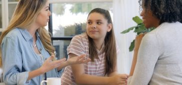 Mom gestures as she discusses her teenage daughter's progress in counseling. The counselor has a pleased expression on her face.